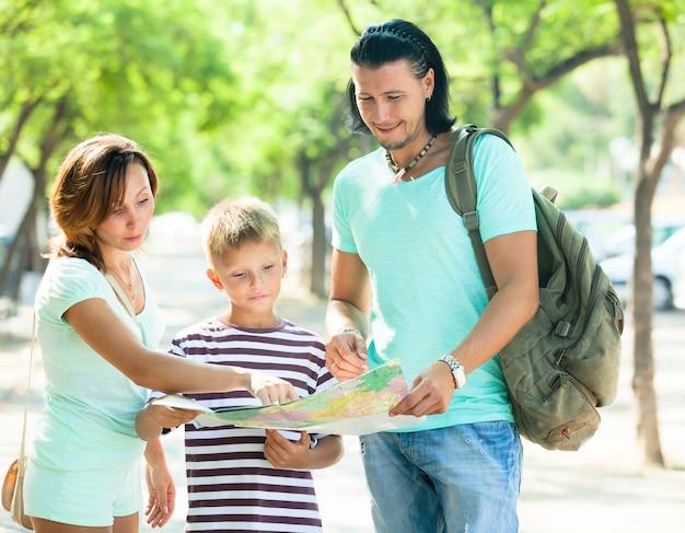Glückliche familie von drei suchweg auf karte