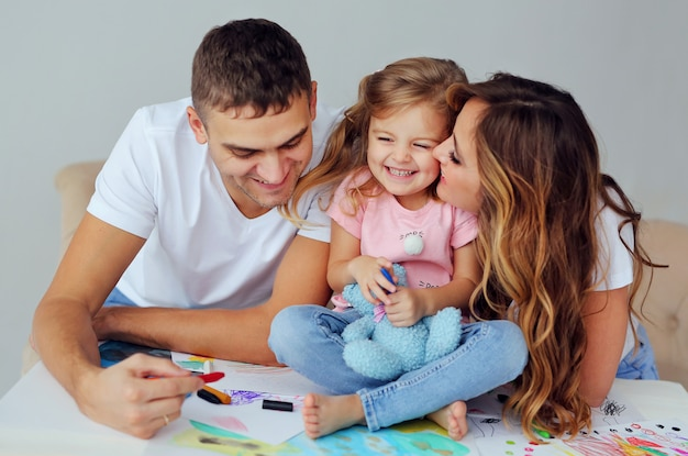 Glückliche familie von europäischem aussehen. lächelnde eltern spielen und lernen, ihr süßes kleines mädchen zu zeichnen. ein mann und eine schöne frau mit einem kind haben spaß.