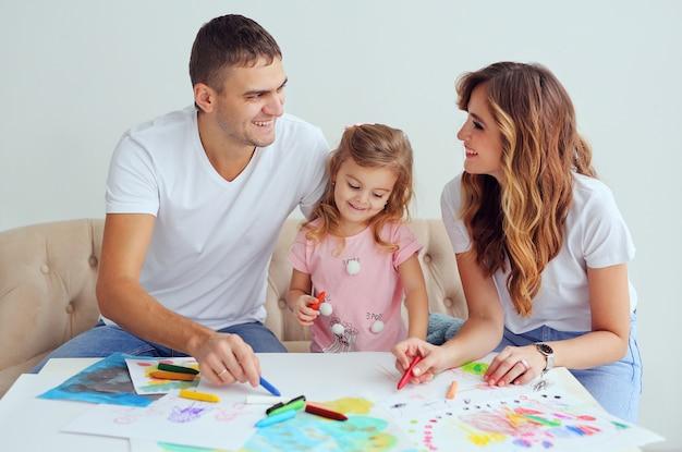 Glückliche familie von europäischem aussehen. lächelnde eltern spielen und lernen, ihr süßes kleines mädchen zu zeichnen.