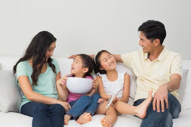 Glückliche familie von mit fernbedienung und schüssel auf sofa im wohnzimmer