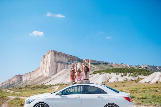 Glückliche familie von mutter und kindern im urlaub in schöner natur auf ihrer autofahrt