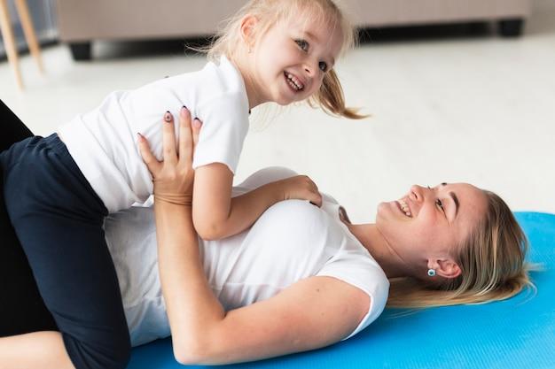 Glückliche familie von mutter und tochter zu hause auf yogamatte