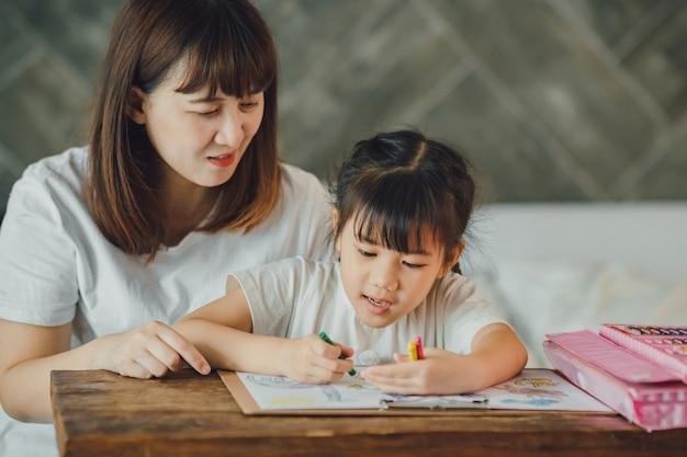 Glückliche familie von mutter und vorschultochter mutter bringt kindern bei, hausaufgaben zu machen konzept für kunst und bildung