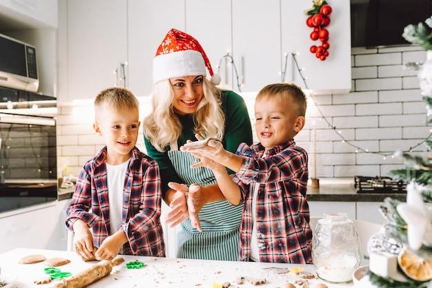Glückliche familie von mutter und zwei kindern zwillings-söhne backen kekse in der küche vor weihnachten in der dekorierten hellen küche.