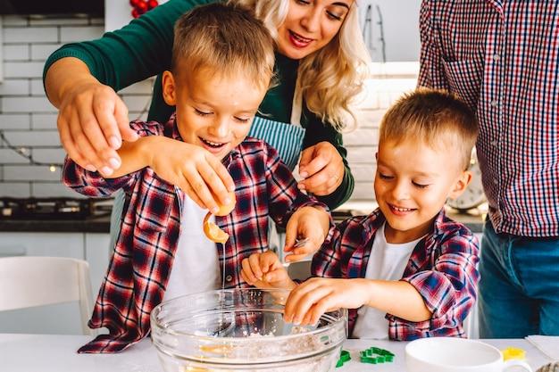 Glückliche familie von mutter, vater und zwei kindern zwillings-söhne backen kekse in der küche vor weihnachten.