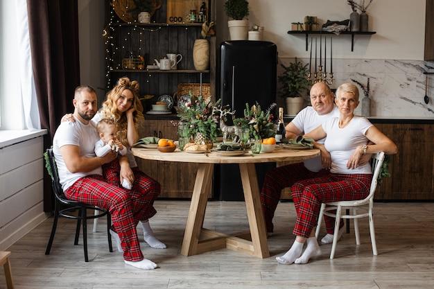 Glückliche familie von vier erwachsenen und einem baby, die neujahr zusammen in der küche am runden tisch feiern.