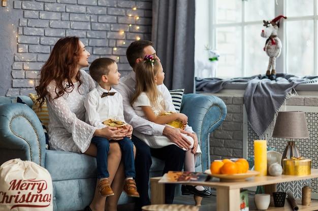 Glückliche familie vor dem weihnachten, das fenster betrachtet