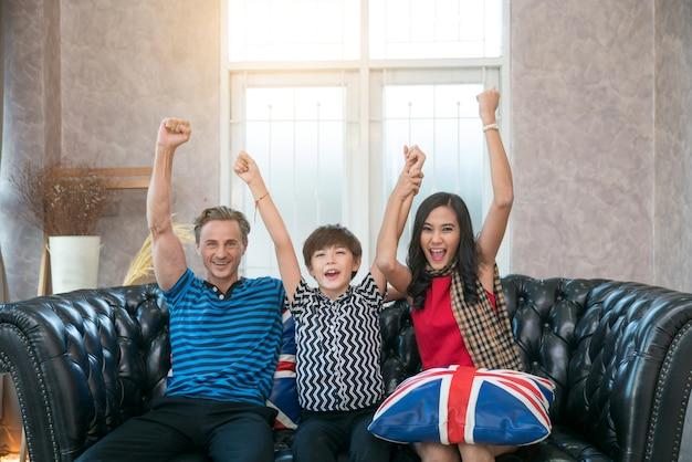Glückliche familie watch fußballspiel im fernsehen auf dem sofa.