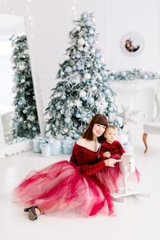 Glückliche familie, weibliche mutter und kleines mädchen, die nahe weihnachtsbaum spielen
