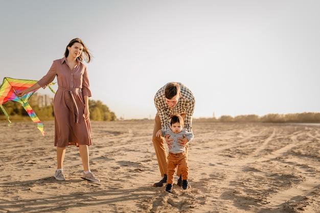 Glückliche familie zu fuß am sandstrand des flusses. vater, mutter, die babysohn auf händen hält und mit drachen spielt.