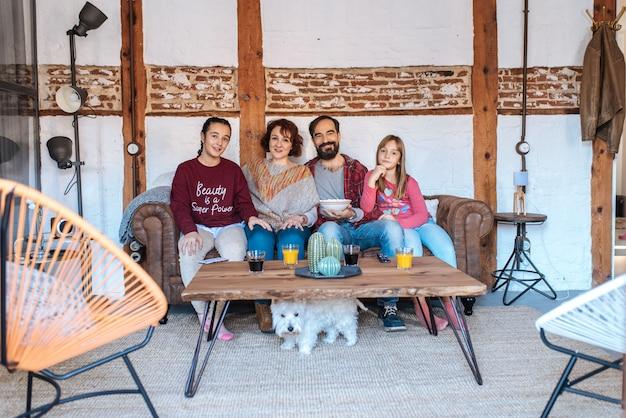 Glückliche familie zu hause, die filme in der couch aufpasst und popcorn isst