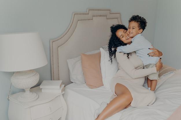 Glückliche familie zu hause. lächelnde schwangere mischlingsmutter im kleid mit lockigem haar, die ihren geliebten süßen kleinen sohn umarmt, während sie auf einem großen weichen bett sitzt. mama und kleines kind verbringen zeit zusammen