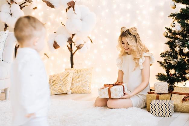 Glückliche familie zu hause vor dem baum. schöne mutter mit einem kind öffnen geschenke. eine frau und ein kleiner junge bereiten sich auf die neujahrsferien vor