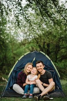 Glückliche familienferien in einem zelt mit einem kind in der natur. mutter, vater und kind genießen einen campingurlaub auf dem land. cept¡onzept von sommerferien und reisen, reise. campingplatz.