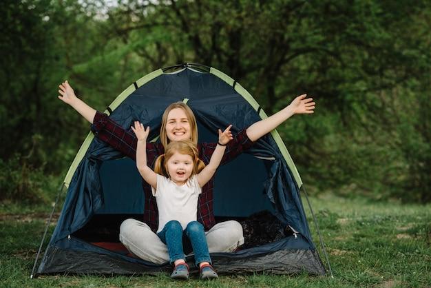 Glückliche familienferien in einem zelt mit einem kind in der natur