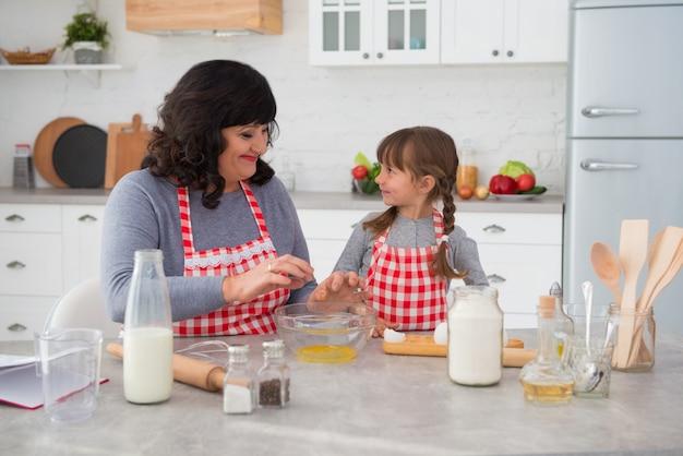 Glückliche familiengroßmutter und kleine enkelin in kochschürzen, die zusammen in der küche kochen