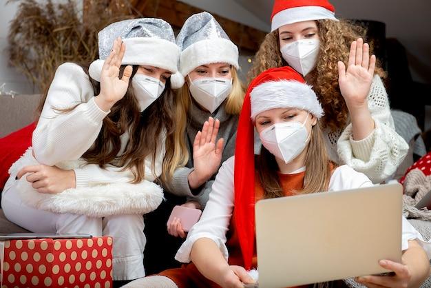 Glückliche familiengruppe von frauen, die weihnachtsmützen und schützende gesichtsmasken tragen, nehmen videoanrufe während der coronavirus-pandemie entgegen. coronavirus und weihnachtskonzept.