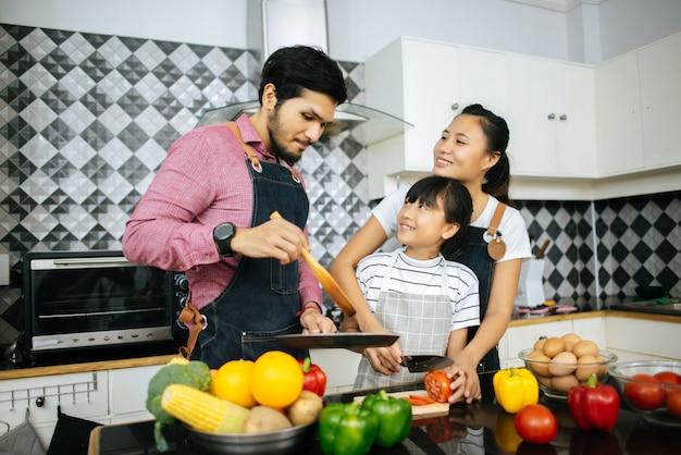 Glückliche familienhilfe, die zusammen zu hause mahlzeit in der küche kocht.