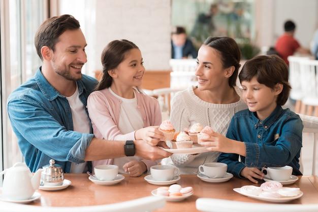 Glückliche familienkinder, die kleine kuchen von der platte nehmen.