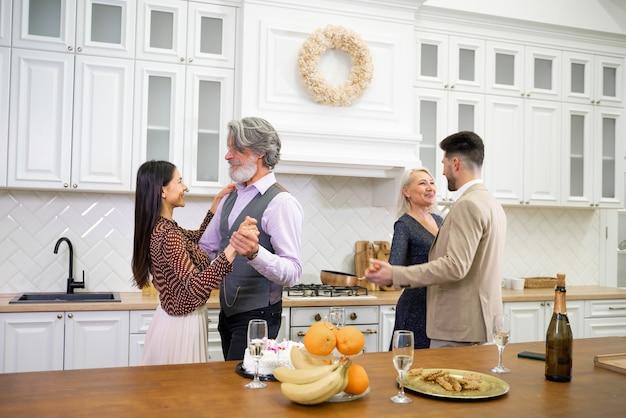 Glückliche familienmitglieder, ältere großeltern und junge paare, die während der familienfeier mit musik tanzen