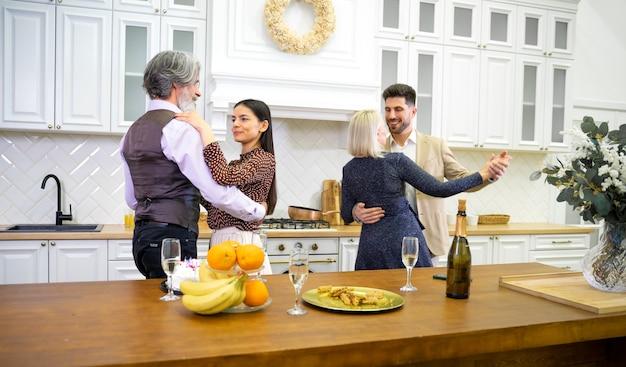 Glückliche familienmitglieder tanzen während der geburtstagsfeier in der küche in der nähe des tisches