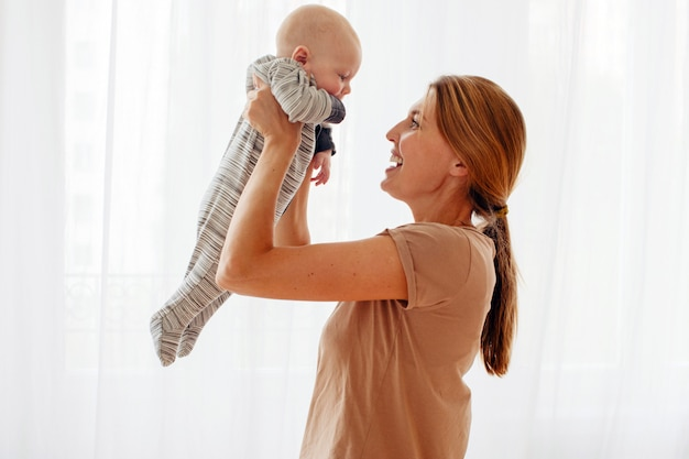 Glückliche familienmutter, die mit neugeborenem baby spielt