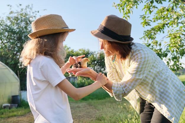 Glückliche familienmutter mit tochter in der natur, frau, die kleine neugeborene küken in den händen hält