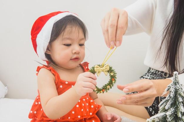 Glückliche familienmutter und -baby, die nach hause an den weihnachtsfeiertagen spielt.