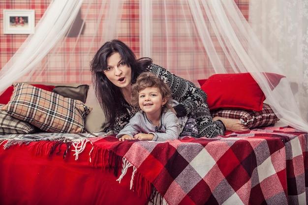Glückliche familienmutter und baby zusammen zu hause der schlafzimmer im winterinnenraum