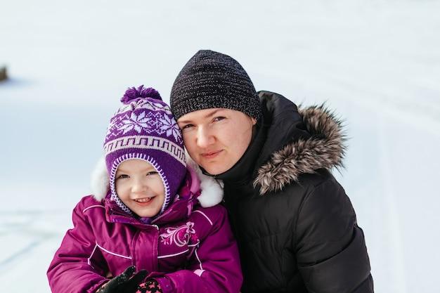 Glückliche familienmutter und babytochter, die draußen im winter lachen spielt