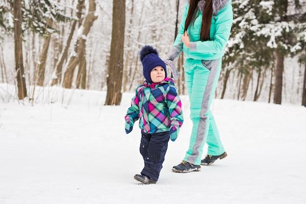 Glückliche familienmutter und babytochter, die im winter draußen im schnee spielt und lacht.