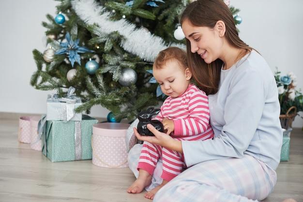 Glückliche familienmutter und kindertochter am weihnachtsmorgen am weihnachtsbaum mit geschenken