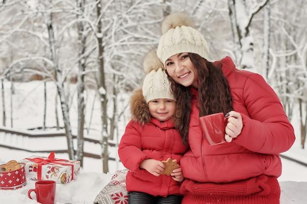Glückliche familienmutter und kindertochter auf winterweg tee draußen trinkend. glückliche familienmutter und kleines kind des babys, die in den winterweihnachtsfeiertagen spielen. weihnachtsfamilie im winterpark.