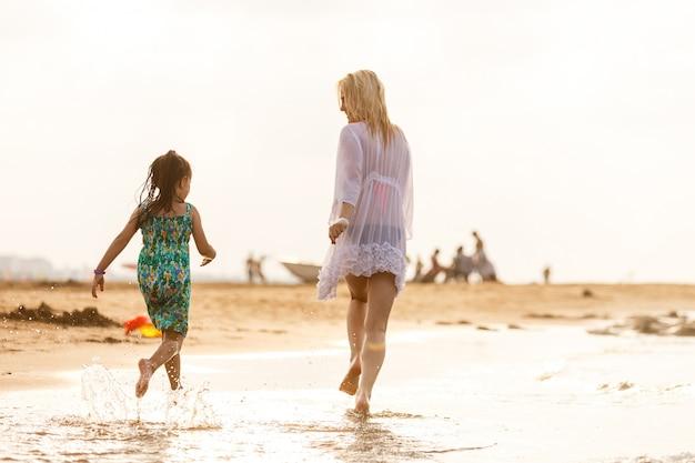 Glückliche familienmutter und kindertochter laufen, lachen und spielen am strand