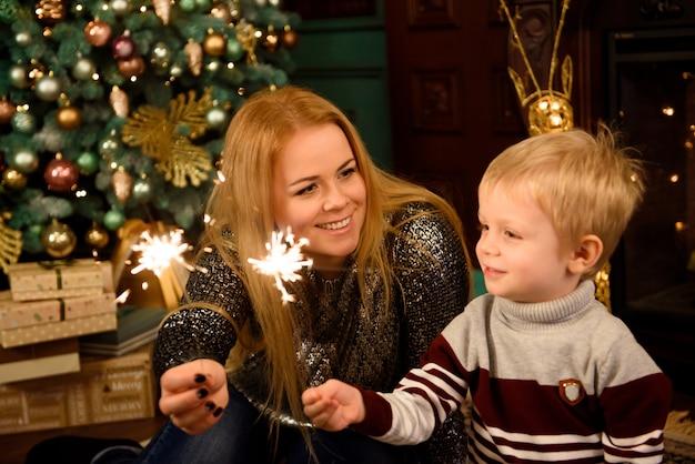Glückliche familienmutter und -sohn mit wunderkerze nahe einem weihnachtsbaum