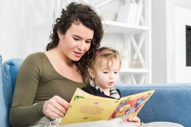 Glückliche familienmutter und -tochter lasen ein buch morgens zu hause
