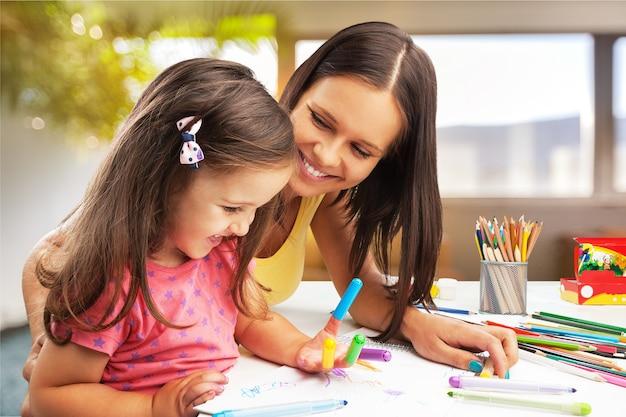 Glückliche familienmutter und tochter malen zusammen. asiatische frau hilft ihrem kindermädchen.