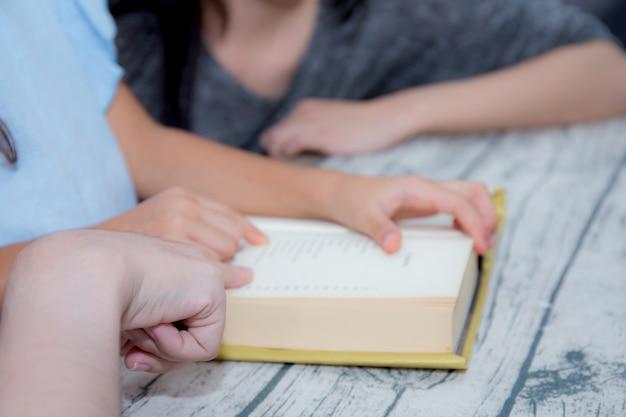 Glückliche familienmutter- und -tochterunterrichten las ein buch zu hause.