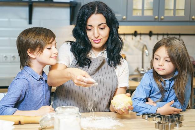 Glückliche familienmutter und zwei kinder, die hausgemachte kekse in der küche kochen