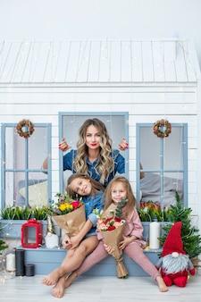 Glückliche familienmutter und zwei schöne mädchentöchter im urlaub in blumen zusammen im haus