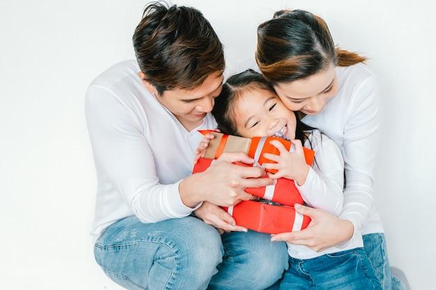 Glückliche familienmutter, vater, kindertochter zu hause mit giftbox weihnachten, guten rutsch ins neue jahr-parteikonzept