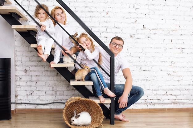 Glückliche familienmutter, vater, zwei töchter und pelzige tierkaninchen, die zu hause auf der treppe sitzen
