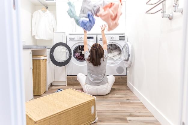 Glückliche familienmutterhausfrau in der waschküche mit der waschmaschine, die oben kleidung wirft