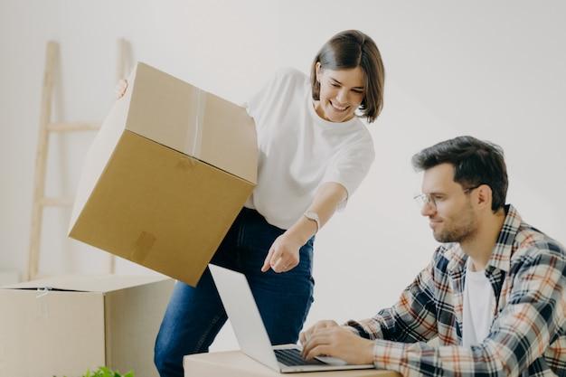 Glückliche familienpaare betrachten aufmerksam laptop-computer