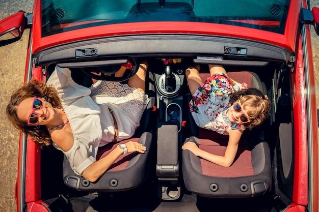 Glückliche familienreise mit dem auto frau und kind, die spaß im roten cabriolet haben sommerurlaub und reisekonzept draufsicht