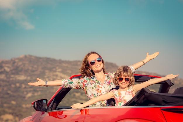 Glückliche familienreisen mit dem auto in den bergen leute, die spaß im roten cabriolet sommerferienkonzept haben