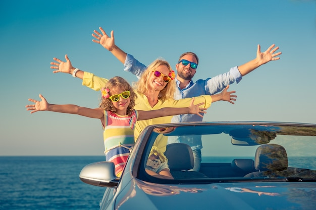 Glückliche familienreisen mit dem auto leute, die spaß im blauen cabriolet sommerferienkonzept haben