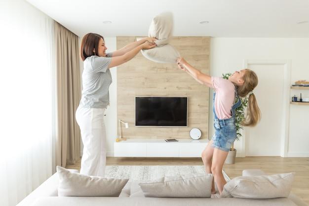 Glückliche familienspiele, alleinerziehende mutter und ihr kindermädchen kämpfen kissen und springen auf couch