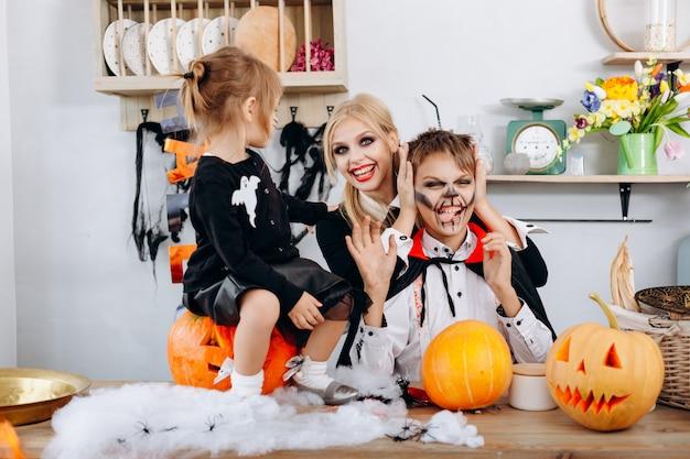 Glückliche familienvorbereitungen zu halloween. junge, der das zungen- und frauenlächeln zeigt