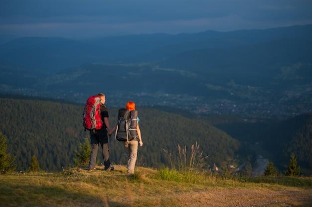 Glückliche familienwanderer mit dem rucksackhändchenhalten und gehen entlang eine straße mit schöner berglandschaft